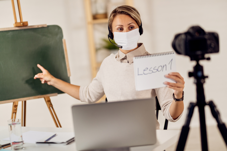 Teacher in a mask records herself teaching a hybrid lesson